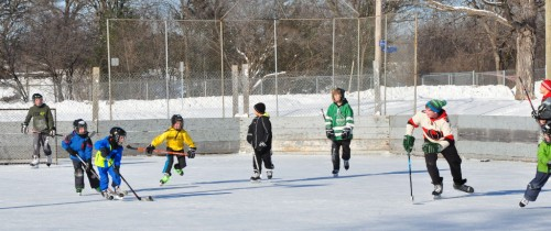 University of Ottawa students help children improve hockey skills on outdoor rink.
